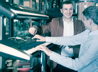 Teenage boy and father choosing best keyboard in musical shop