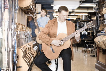 Boy and father choosing acoustic guitar