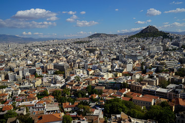 View of beautiful Athens cityscape from Acropolis seeing lowrise building architecture, Mount Lycabettus, mountain, blue sky and floating white cloud background