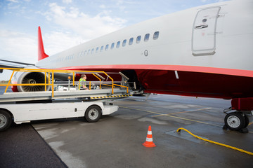 Conveyor Truck By Commercial Airplane On Wet Runway