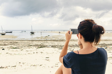 Young woman photographs a mobile phone ocean