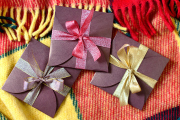 Holiday gifts for Christmas and New Year on the background of plaid in red and yellow colors.