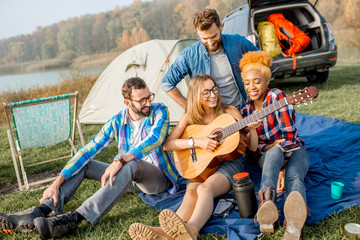 Multi ethnic group of friends dressed casually having fun playing guitar during the outdoor recreation with tent, car and hiking equipment near the lake