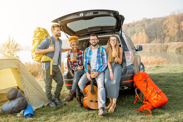 Multi ethnic group of friends sitting at the car trank during the outdoor recreation with tent and hiking equipment near the forest