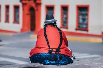 Donna peruviana seduta di spalle