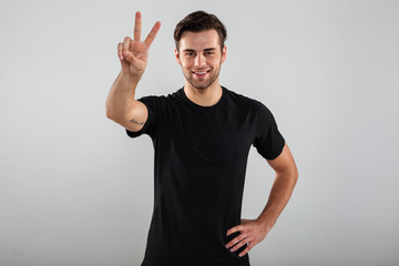 Portrait of a casual man standing and showing peace gesture