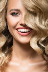 Wall Mural - Blonde woman with curly beautiful hair smiling. Close up portrait.