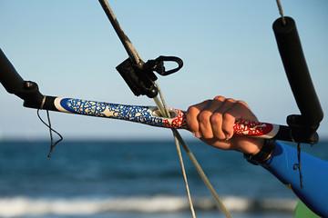 Kitesurfer ready for kitesurfing rides in blue sea detail control bar