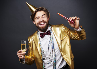 Portrait of smiling man holding champagne flute and party blower .