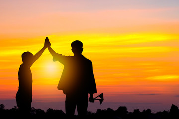 Success ans achievement concept, Silhouette of  men holding two flag in team gesture and go forward to goal in sunset.