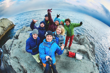 funny laughing friends near the sea in winter taking selfie together