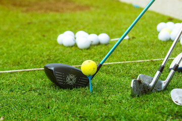 Golf ball on tee ready to be shot with golf club at sunrise in morning with copy space