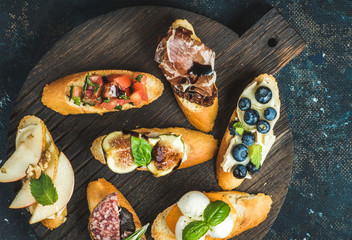 Italian crostini with various toppings on round wooden serving board over black plywood background, top view
