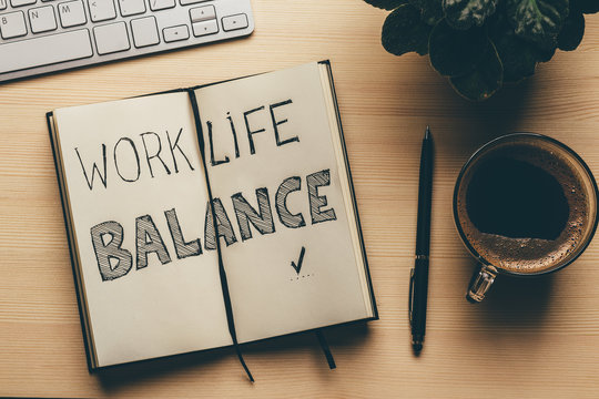 Work Life Balance - handwrite words in open notebook, pen, cup of coffee, top view. Lifestyle success strategy concept