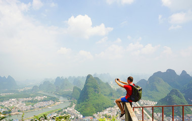 Hiker with backpack take a picture on his smartphone from top of the hill with beautiful view on Yangshuo city with mountains around. Yangshuo, China