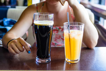 Woman drinks cocktail and beer in cafe