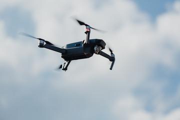 Quadrocopter Drohne vor wolkigem Himmel