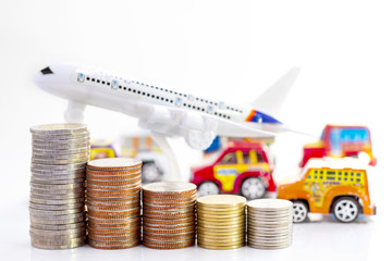 Coins stack with airplane and toy car on white background.