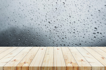 Wood table on blur raindrop background used for display product