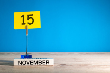 November 15th. Day 15 of november month, calendar on workplace with blue background. Autumn time. Empty space for text