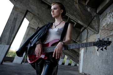 Beautiful girl with red bass guitar. Rockstar style