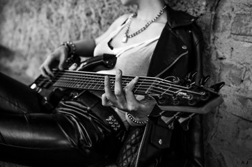 Close-up photo of electric guitar player in leather jacket. Black and white photo