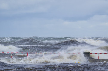 STORM - Handrail on breakwater among rough waves