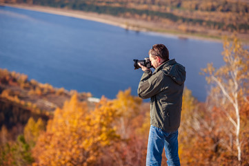 a man stands on top of a mountain and takes a picture of the landscape