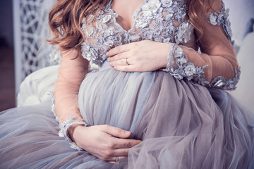 Beautiful pregnant girl in luxurious dress, holding her hands belly. Closeup female belly