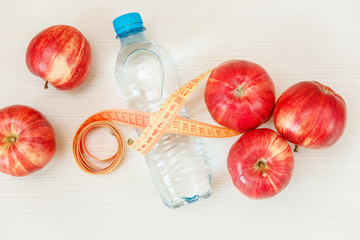 Fresh apples,botle of water and tape measure.Diet and fitness concept.White table.Top view.