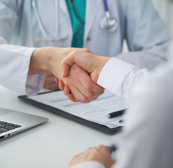 Doctor and patient shaking hands, close-up.  Physician talking about medical examination results. Medicine, healthcare and trust concept