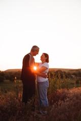 Couple holding hands at sunset enjoying romance and sun.