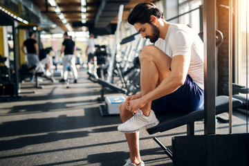 Handsome bearded man ties up his shoelaces on sneakers at the gym before exercises.