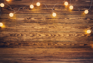 Old wooden planks with christmas decoration. Brown background with lightbulbs Wall mural