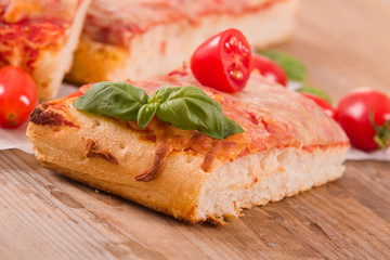 Italian pizza with cheese, tomatoes and fresh basil.