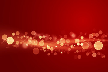 Abstract shiny color gold light wave design element with glitter bokeh effect on dark red background.