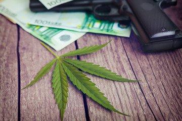 Marijuana leaf with gun and money bills
