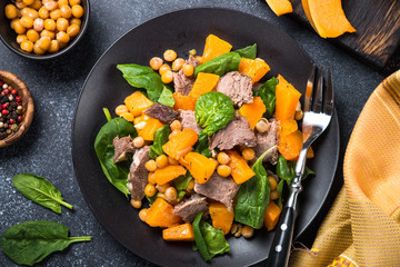 Warm salad with pumpkin, baked beef, spinach and chickpeas.