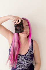photographer girl with pink hair on a photo shoot with a camera