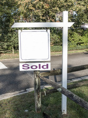 Blank for sale sign with a sold sign under it