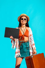 bohemian traveler with black board and suitcase