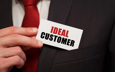Businessman putting a card with text IDEAL CUSTOMER in the pocket