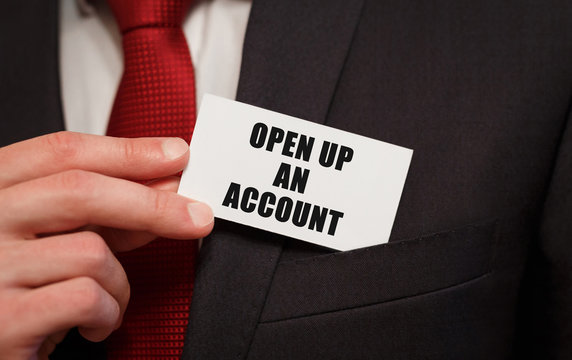 Businessman putting a card with text OPEN UP AN ACCOUNT in the pocket