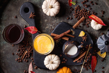 Ingredients for cook spicy pumpkin latte. Glasses with black coffee, pumpkin milk, jug of cream on black serving board. Spices, coffee beans, autumn leaves above over dark background. Top view, space.