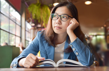 Woman in Blue shirt thinking while reading a book.