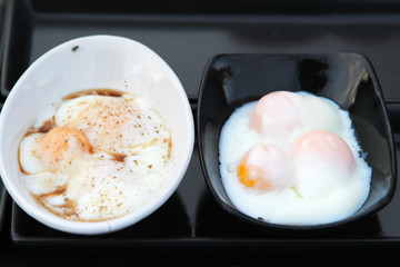 Street food, poached eggs sprinkle pepper in white bowl at market.