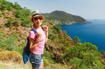 Young woman traveler with backpack standing on cliff's edge and looking to a mediterranean sea landscape, summer vacation concept
