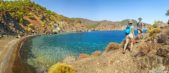 Group of Hikers walking by Lycian Way trail along wild beach and mountains in Turkey