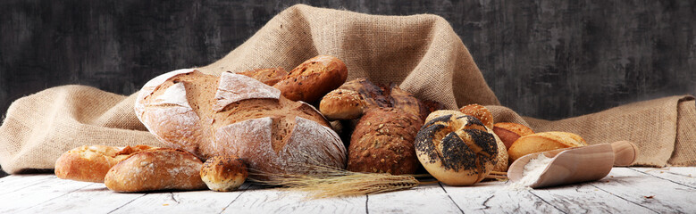 Poster de jardin Boulangerie Assortment of baked bread and bread rolls on wooden table background.
