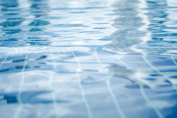 the water surface of the blue pool. background, wave. Clean and bright water in swimming pool and sparkling light reflection